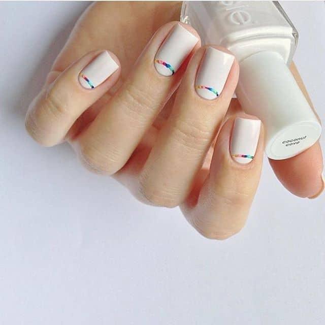 Ярко-белый маникюр на короткие ногти с мини-радугами фото